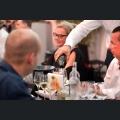 Service schenkt Gästen Wein ein